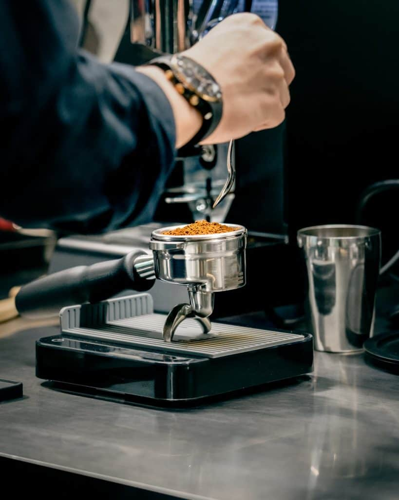 person pouring coffee on silver coffee cup